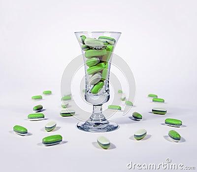 Green pills in a glass