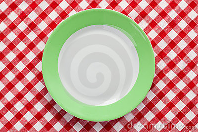 Green plate on checkered tablecloth
