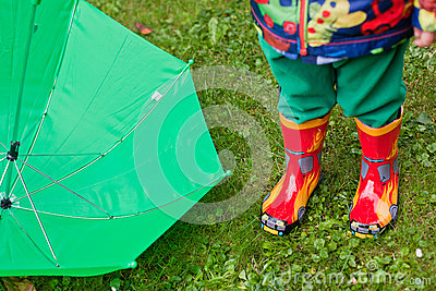 Green rain umbrella and children autumn boots