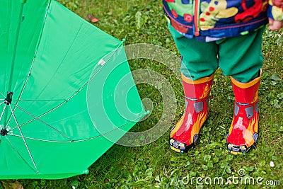 Green rain umbrella and children autumn boots