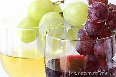 Green and red grapes on the white and red wine glasses