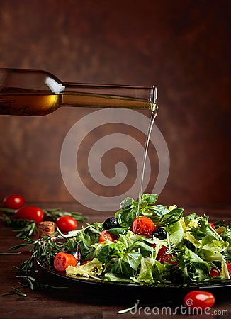 Free Green Salad With Olive Oil Pouring From A Small Bottle. Stock Image - 108731021