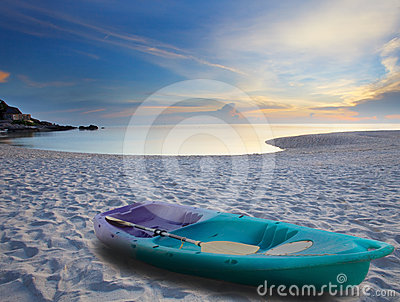 Green sea kayak on sand beach