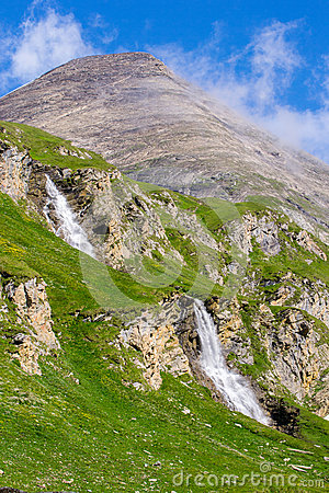 Green slopes with two waterfalls and a mountain peak