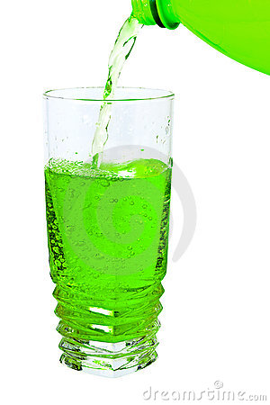 Green soda in a tall glass, pour from the bottle