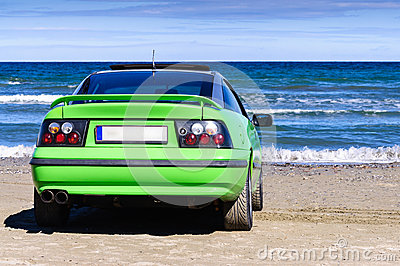 Green sport car on beach