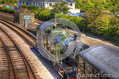 Green steam train engine and carriage on railway tracks in vivid colourful HDR