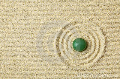 Green stone on surface of yellow sand