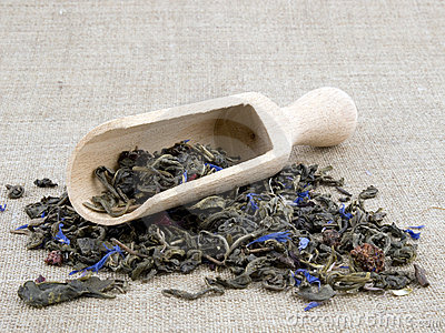 Green tea and wooden shovel on linen background