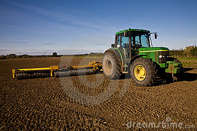 Green tractor with harrow on tilled field Editorial Photography