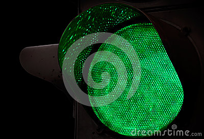 Green traffic light above black background