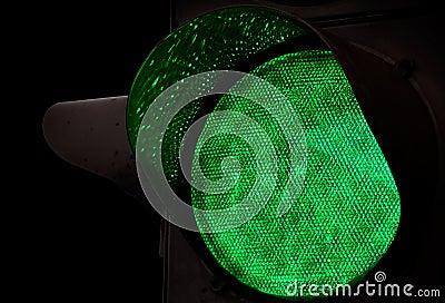Green traffic light above black background
