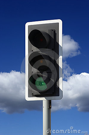 Green traffic light on blue sky