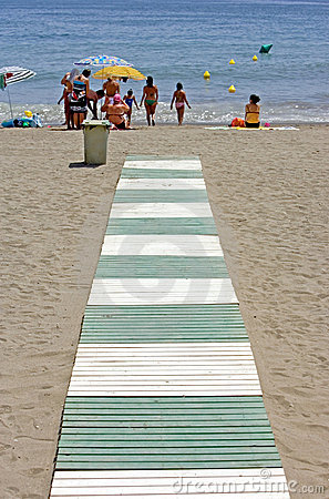Green and white path leading to beach in Spain