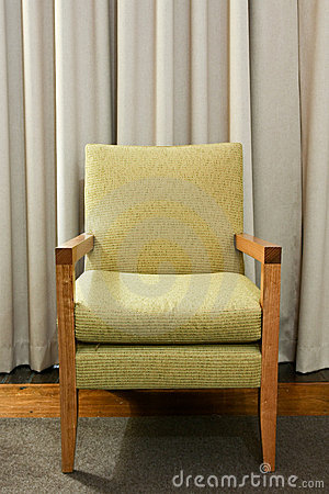 Green wooden and upholstered chair on rug.