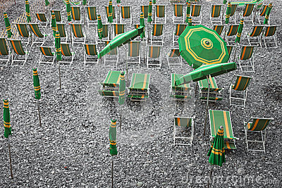 Green and yellow beach umbrellas and deckchairs on stony beach