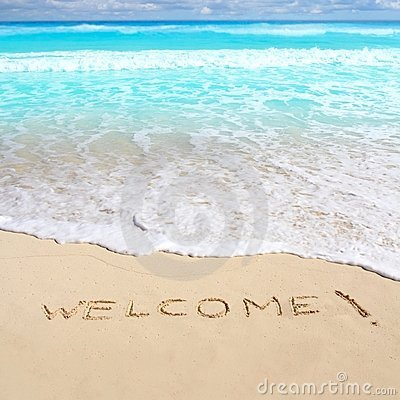 Greetings welcome beach spell written on sand
