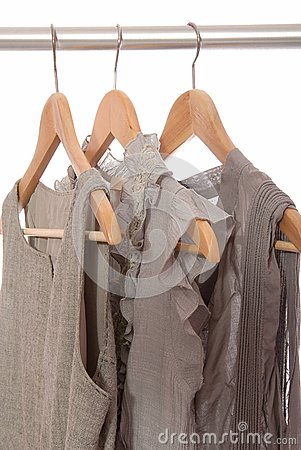 Grey dresses are on  hangers.