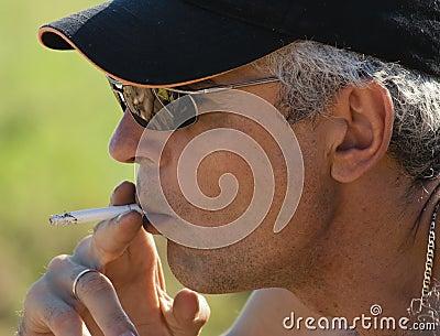Grey man smokes a cigarette