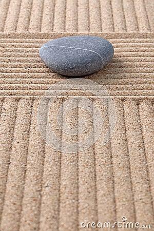 Grey pebble on raked sand vertical