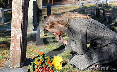 Grief-stricken lady with flowers at grave