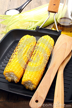 Grill corn and spatula in frying pan.