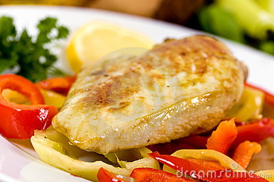 Grilled chicken breasts on a plate with fresh vege