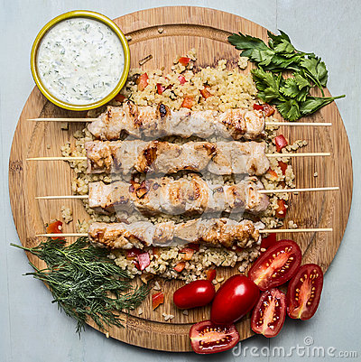 Free Grilled Chicken On Skewers With Garlic Sauce And Bulgur Dill Parsley And Tomatoes On A Cutting Board Wooden Background Top View Stock Images - 61011854