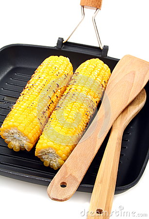 Grilled corn and wooden spoon in the pan.