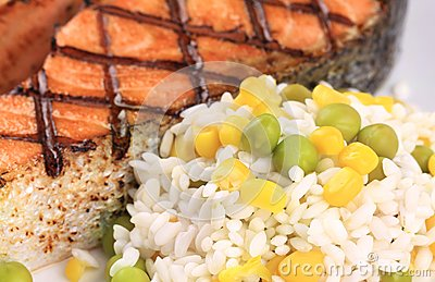 Grilled salmon steak with rice on plate.