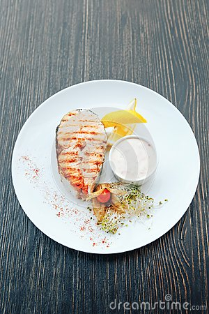 Free Grilled Salmon Steak With Sauce And Lemon On A White Plate. Background Wooden Table Royalty Free Stock Image - 124072616