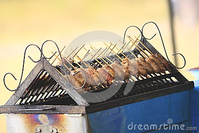 Grilled sausage over a hot barbecue grill.