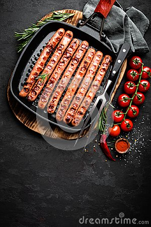 Free Grilled Sausages Bratwurst In Grill Frying-pan On Black Background. Top View. Traditional German Cuisine Royalty Free Stock Photo - 106057925