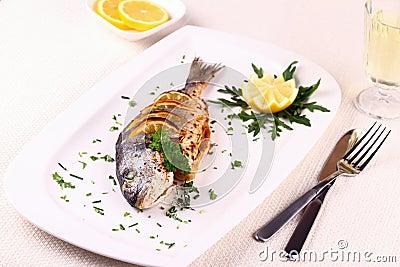 Grilled sea bream fish, lemon, arugula on plate Stock Photo