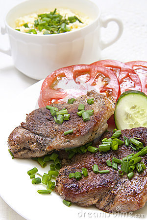 Grilled steak with fresh vegetables in white plate