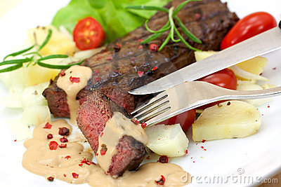 Grilled strip steak with tomato and salad