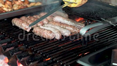 Grilling meat. Outdoor lit barbecue grilling sausages and meat stock video