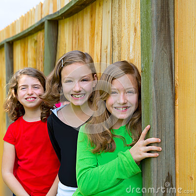 Grils group in a row smiling in a wooden fence
