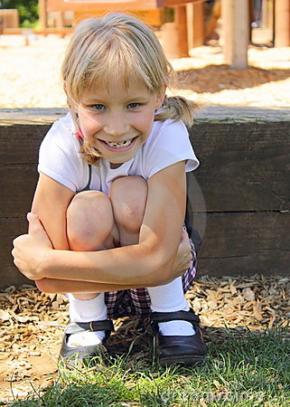 Grinning Little Blond Girl Playing in a Playground