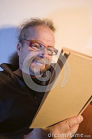 Grinning man behind book