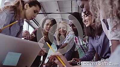 Großaufnahme des jungen Geschäftsteams mit dem weiblichen Teamleiter, der nahe der Tabelle, aktiv gedanklich lösend zusammenarbei stock video footage