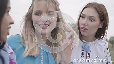 Großaufnahme von drei Freundinnen in den Sommerkleidern mit der Stickerei, die auf dem Gebiet sitzt und spricht Konzept von stock video footage