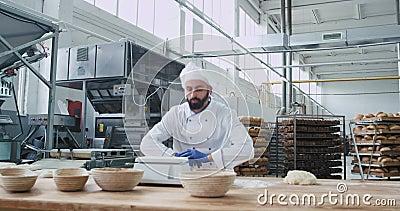 Große Bäckerei Industrie lustiger Bäckbäcker mit Bart, der den Teig zum Backen von Brot und Tanzen gleichzeitig vorbereitet. stock video footage