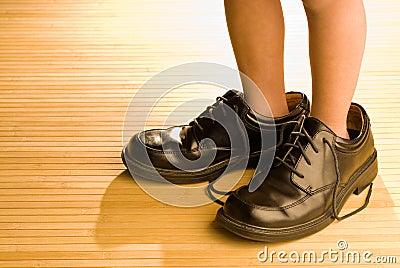 Große Schuhe zum zu füllen, Füße des Kindes in den großen schwarzen Schuhen