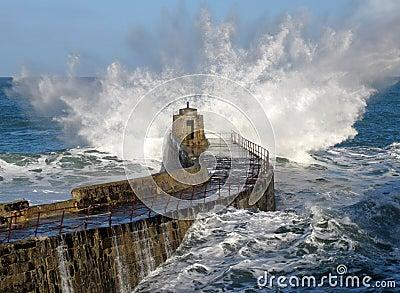 Großes Wellenspritzen auf Portreath Pier, Cornwall Großbritannien.