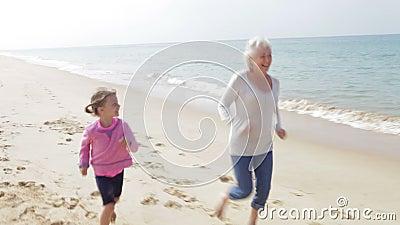 Großmutter und Enkelin, die zusammen entlang Strand laufen