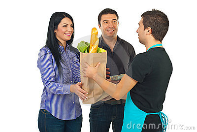 Grocery clerk giving bag to couple
