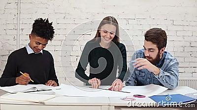 Groep jong binnenlands ontwerpersteam die in creatief bureau samenwerken Jonge beroeps die schetsen het zitten maken stock footage