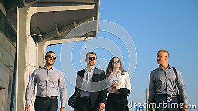 Groep jonge gelukkige zakenlieden die in stadsstraat aan luchthaventerminal lopen Collega's die op zijn manier aan zaken zijn stock videobeelden