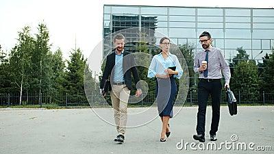Groep jonge zakenmensen die naar buiten wandelen en een gesprek voeren stock videobeelden